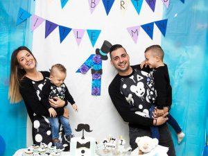 Семейство с еднакви дрехи празнуващи детски роцден ден.