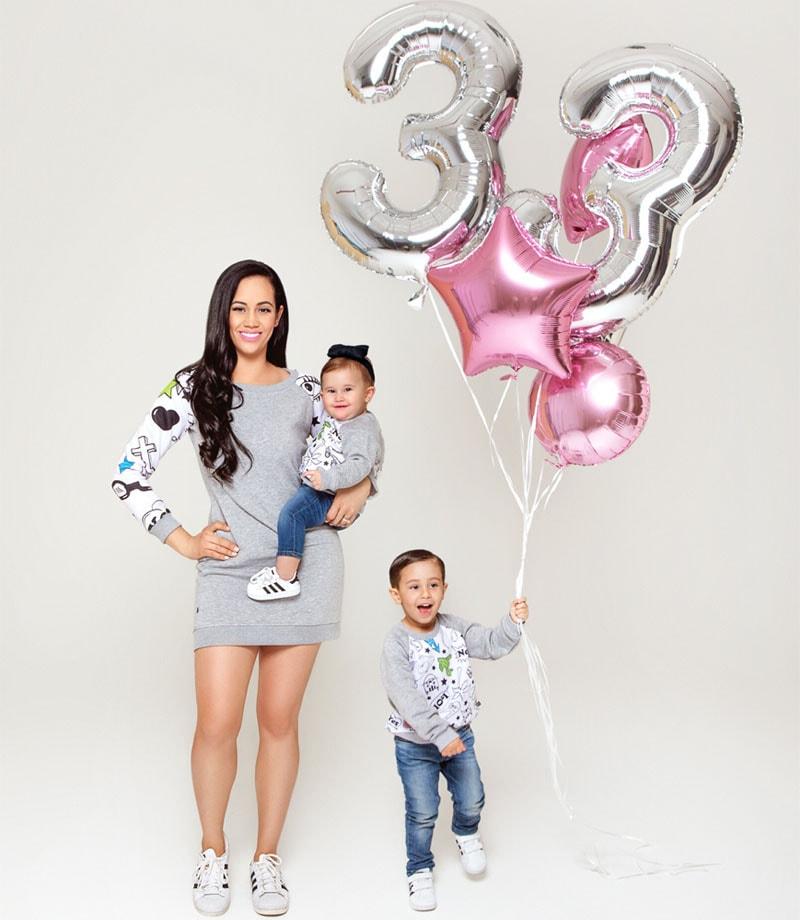 Майка с 2 деца позиращи с еднакви дрехи в студио с балони.