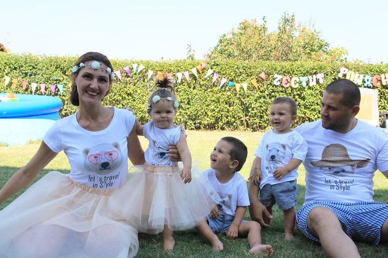 Семейтво облечено с тенсики с мечета седнали на тревата пред басейн.
