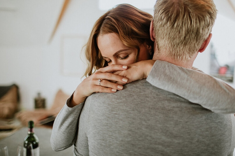 Прегърнати мъж и жена с годежен пръстен.