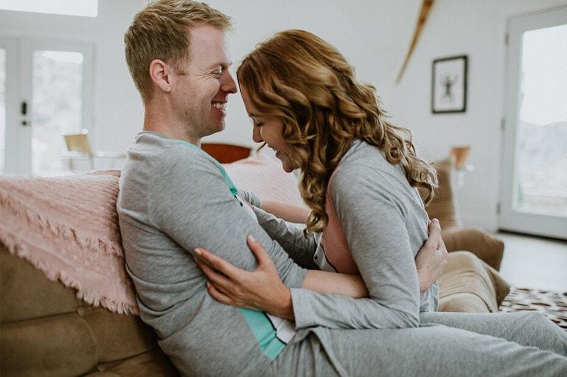 Влюбени мъж и жена прегърнати по пижами.