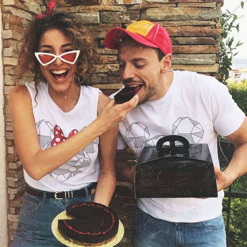 Жена и мъж с тенсиски на Мики Маус хапват шоколадова торта.