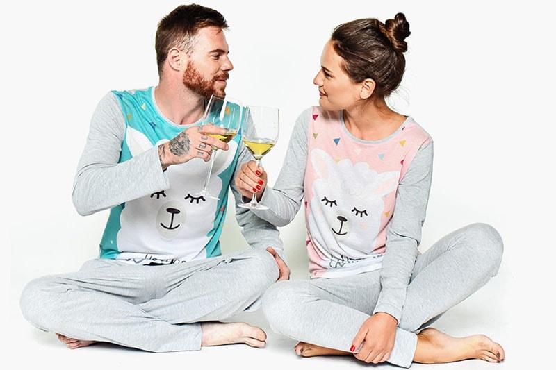 Мъж и жена облечени в еднакви пижами пият вино