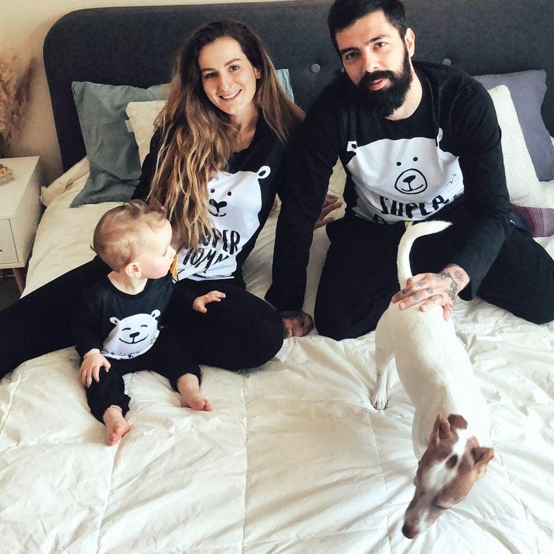 Семейство по пижами, седят на спалня с кучето си.