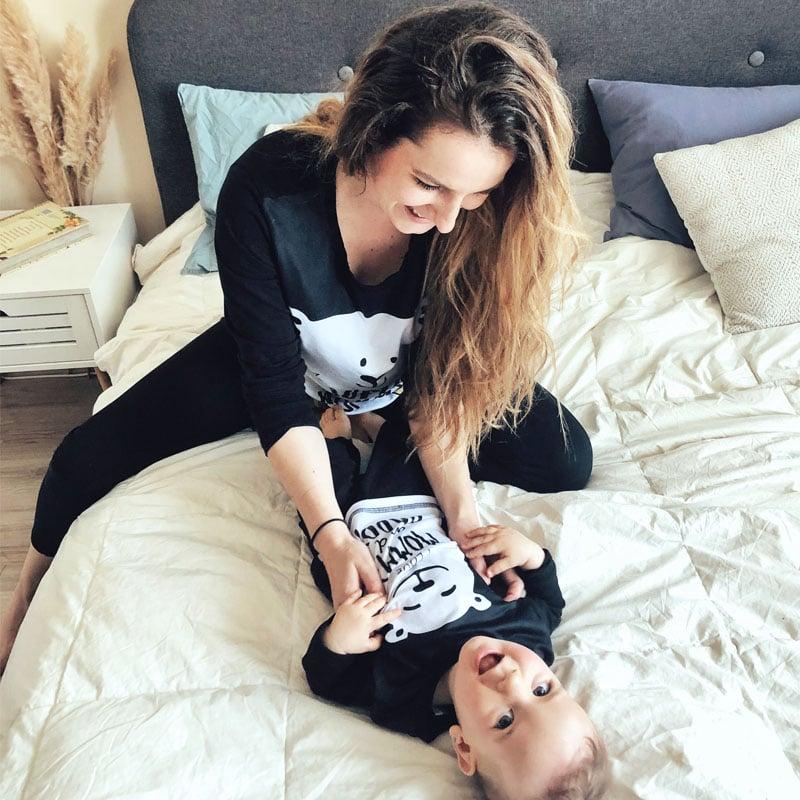 Майка гледа бебе, легнало на спалнята