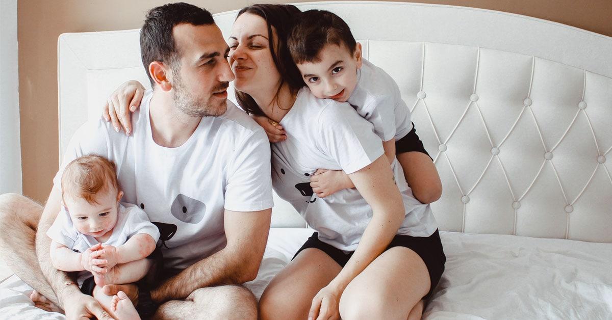 Семейство с деца се гушкат на легло по пижами