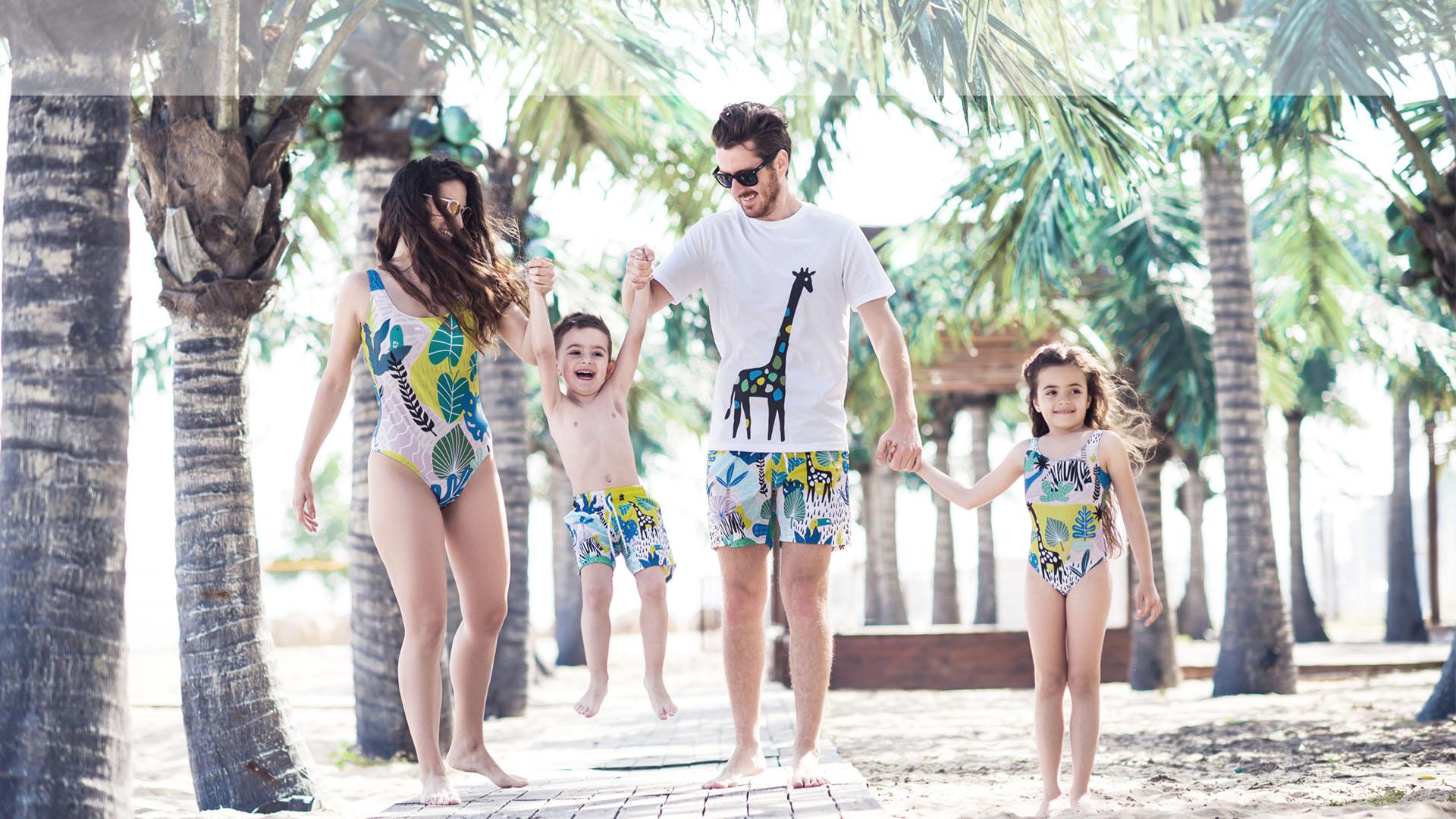 Семейство се разхождат по плажа облечени с еднакви бански