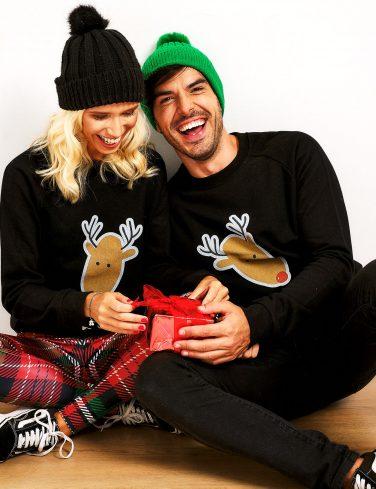 момче и момиче с коледни пуловери отварят подарък