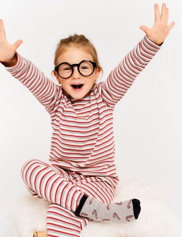момиченце с очила облечено с коледна пижама