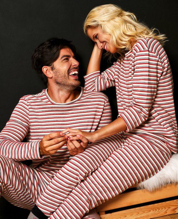 мъж подава пръстен на жена облечени в коледни пижами