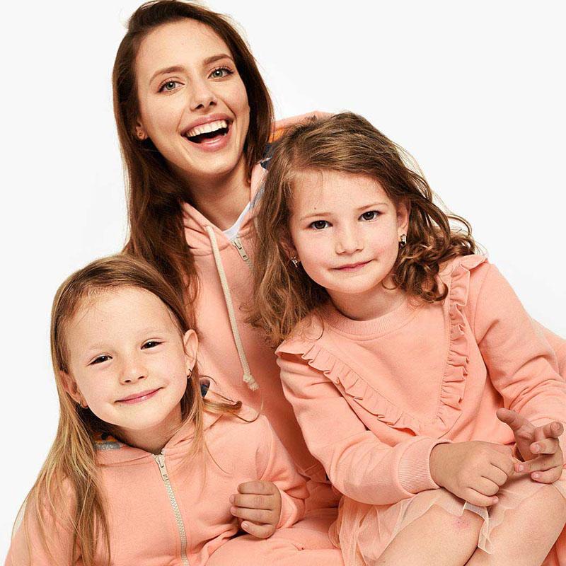 Майка с две дъщери, облечени в еднакви блузи
