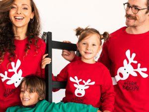 Четиричленно семейство с две деца облечени с червени коледни пуловери позират в студио