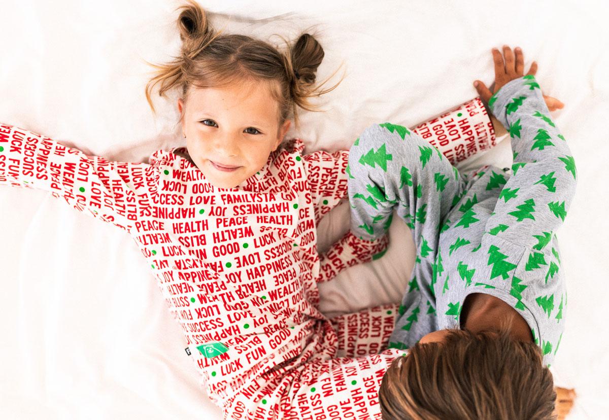 момиченце облечено в коледна пижама лежи на спалня с разперени ръце и се усмихва до него друго дете го гледа
