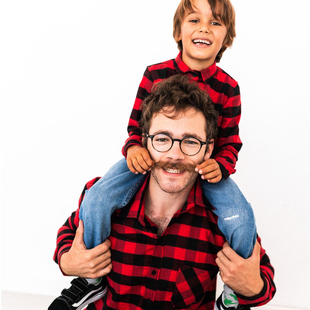 дете седнало върху баща си и го държи за мустака
