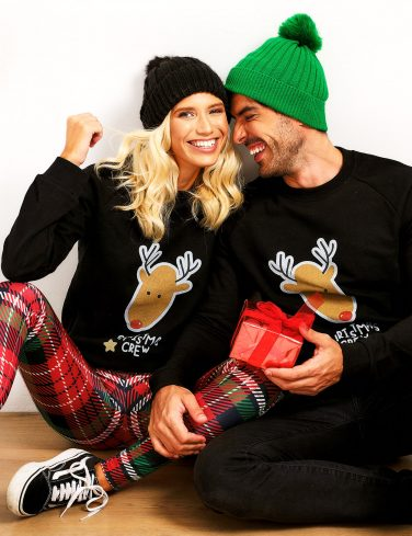 Couple with Christmas sweaters holding a gift