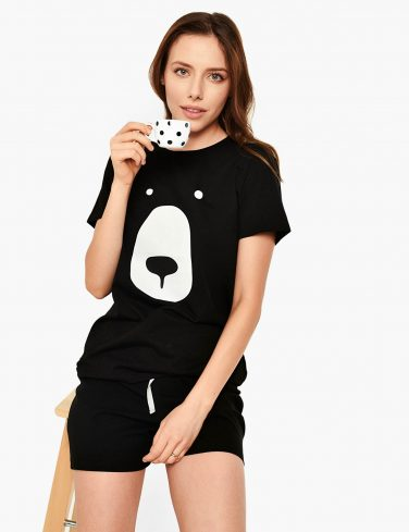 woman holding cup of coffee in bear pajama
