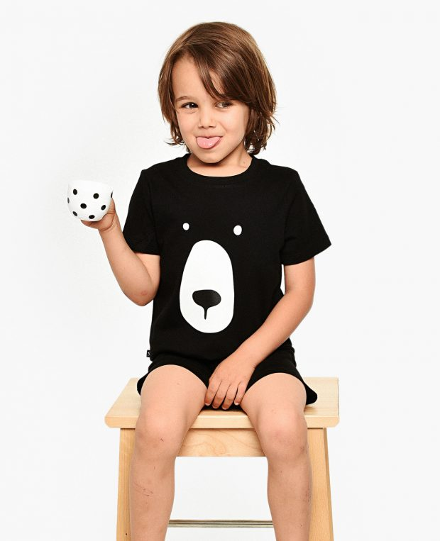 boy with a cup in bear pajama